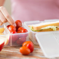 close up of woman with food in plastic container